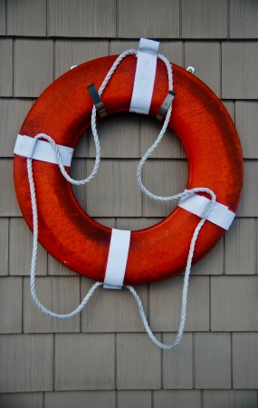 flotation: weathered orange life preserver, or personal flotation device, hanging on a wooden wall