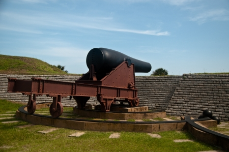 Canon pointing towards sea at Fort Moultrie.  Canon is on top a large metal structure with wheels that can turn the canon's position.  canonballs are present in front of canon.  Protecting wall is visible photo