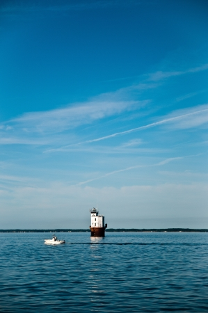 Small white power boat motoring by a lighthouse in the middle of the chesapeake bay with a beautiful blue sky.  The Smith Point Lighthouse photo