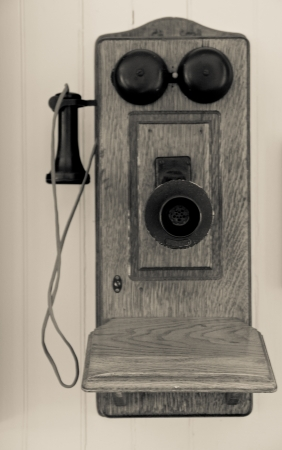 old fashioned: Antique stlye crank telephone made of wood and metal, mounted on a white wall   Set in Black and White Stock Photo