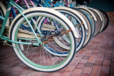 Several brightly colored bicycles lined up along a bike rack  Stock Photo