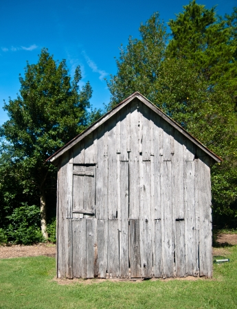 Old wood shack or cabin in the woods against a beauitful bright blue sky photo