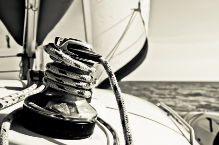 Black and white photograph of a line or rope wrapped three times around a large metal cleat