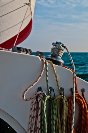 Several lines or ropes coiled and tied to a sail boat.  There is one line that is wrapped around the winch and a red and white sail is set and visible in the background Stock Photo - 16577355