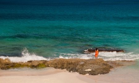 beach wrap: woman in orange wrap standing on rocks watching the ocean at a beautiful white sand beach with turquiose waters