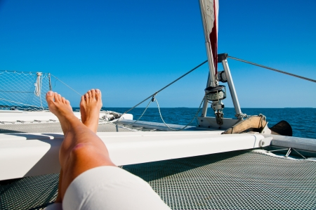 feet crossed: woman lounging on a catamaran sailboat trampoline with her feet propped up and crossed   calm blue ocean and cloudless blue sky are in the background  copy space available