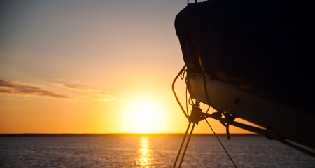 Sun setting over the ocean with the boom and mainsail of a sailboat in the foreground.  copy space available Stock Photo - 18690743