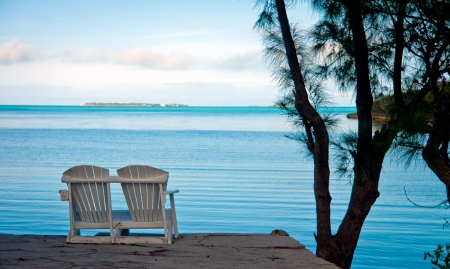 adirondack chair: Two white adirondack chairs at the edge of a stone patio overlooking the ocean in the Bahamas