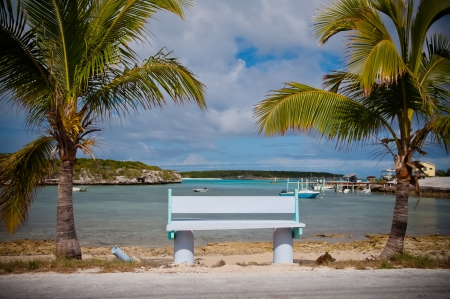 either: Green and white bench with palms trees on either side, overlooking the ocean in the islands of the bahamas. A few small boats are moored in the bay and the dock is visible on the right. Stock Photo