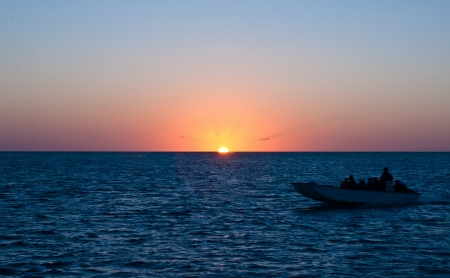 small fishing boat with many people on it, passing in front of a setting sun over the ocean on a beautiful night in the bahamas photo
