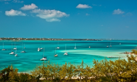 many sailboats and power boats anchored in crystal clear turquoise waters of the bahamas