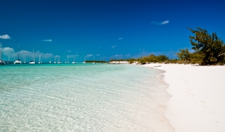 beautiful turqouise waters of the islands of the bahamas with many sailing and fishing boats anchored in the harbor of George Town, Exumas   white sand beach and crystal clear blue sky has room for copy space