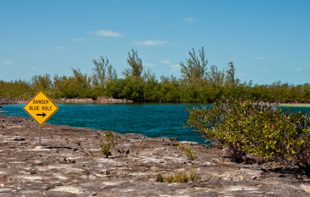 Landscape image of a yellow danger sign warning about a blue hole  in the islands of the bahamas  Stock Photo