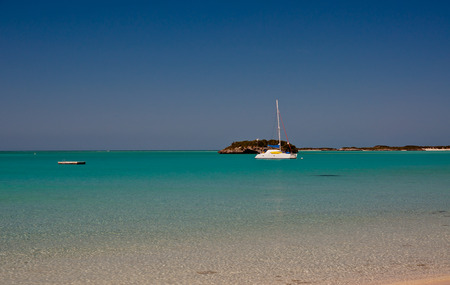 one catamaran sailboat anchored in the caribbean off the coast of the bahams.  beautiful shades of turguoise waters and clear blue sky.  copy space available