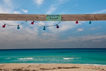 Sign reading Paradise Found on a piece of wood with colorful lights hanging about a beautiful beach in the caribbea