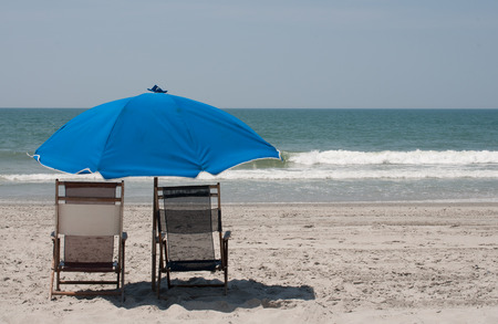 beach chairs: Two beach chairs with a blue umbrella set in beautiful white sand with blue ocean waters and clear sky in background.  copy space available