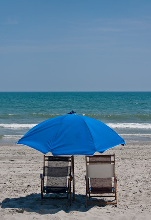 Two beach chairs with a blue umbrella set in beautiful white sand with blue ocean waters and clear sky in background.  copy space available