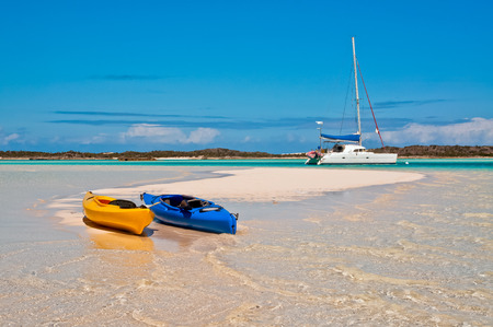 blue and yellow kayaks beached along the white sand beach with catamaran sailboat anchored in the background.