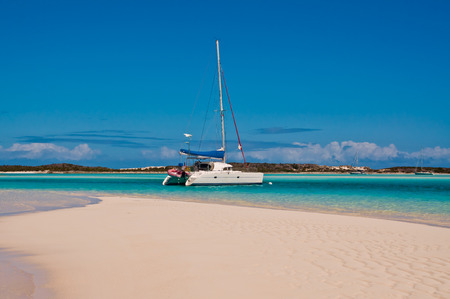 White Catamaran sailboat anchored or moored in the turquoise torpical waters with white sand beach in the foreground