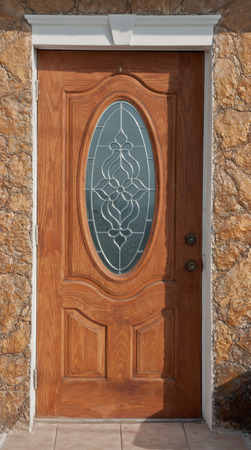 ornate wooden front door with glass window.  white trim and brick front of house