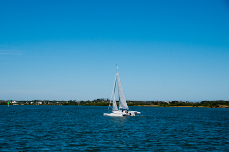 man and woman sailing a white trimaran multihull sailboat on the intracoastal waterway in Florida, USA Standard-Bild
