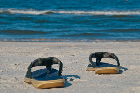 A Pair of Blue Flip Flops on the sand at the beach with the ocean waves in the background.  Copy space available Stock Photo