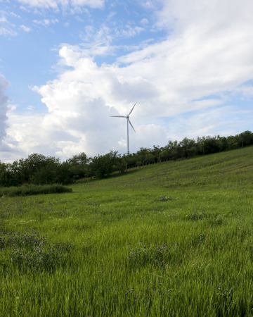 Green field, blue cloudy blue sky and wind farm Imagens