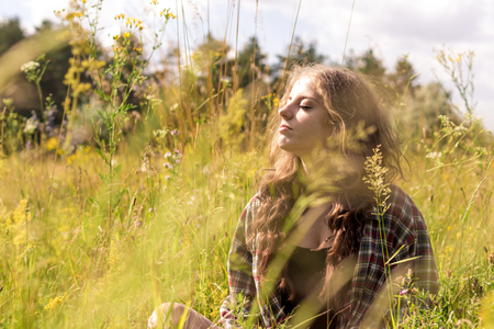 unworried: Beautiful young woman with closed eyes and long curly brown hair dressed in a check shirt is sitting on a meadow in high grass and gentle wild flowers
