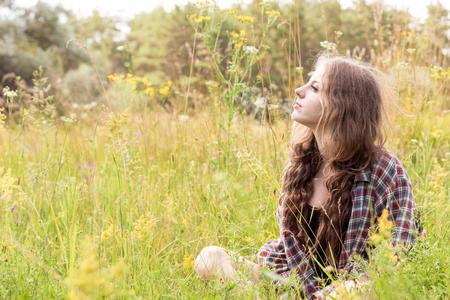 snění: Krásná mladá žena s dlouhými kudrnatými hnědými vlasy oblečená v kontrolní košili sedí na louce ve vysoké trávě a jemných divokých květech Reklamní fotografie