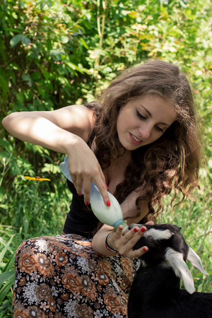 Attractive young woman is feeding a baby goat with milk from the bottle. Vertical orientation. Stock Photo