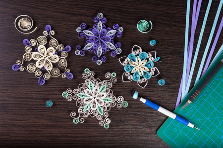 Handmade paper snowflakes with tools for quilling (paper strips, slotted tool, knife, cutting mat) on dark wooden background. Preparation for Christmas.