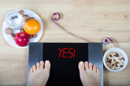 surfeit: Digital scales with female feet on them and signyes! surrounded by glass of water, plates with nuts, fruits, muesli and measuring tape. Demonstrates results of eating healthy food and sticking to healthy lifestyle.