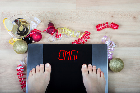 Digital scales with female feet on them and signomg! surrounded by Christmas decorations and glass of vermouth. Shows how alcohol and unhealthy lifestile during xmas holidays effect our body. 版權商用圖片