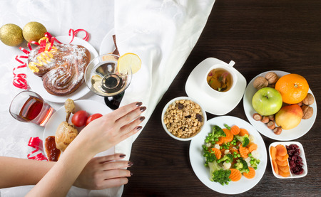 Table with healthy and unhealthy food and alcohol. Woman hands covering the part with harmful dishes and drinks with table cloth. Dieting after christmas and new year celebration. Stock Photo