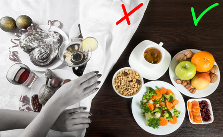 surfeit: Table with healthy and unhealthy food and alcohol. Woman hands covering the part with harmful dishes and drinks with table cloth. Dieting after Christmas and New Year celebration. Stock Photo