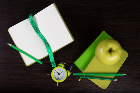 Open notebook, pencils clock and apple on dark wooden background. Different tints of green. Top view. Flat lay. Can be used as a field for text input, notebook cover.