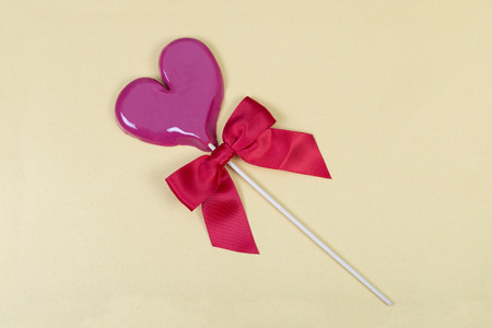 sateen: Light violet heart shaped lollipop with red sateen bow on light yellow background with slight shimmer.  Stock Photo
