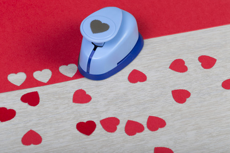 Figured plastic paper punch and handmade red hearts. Preparation of decorations for Valentines day, wedding or other romantic event. Close shot. Stock Photo
