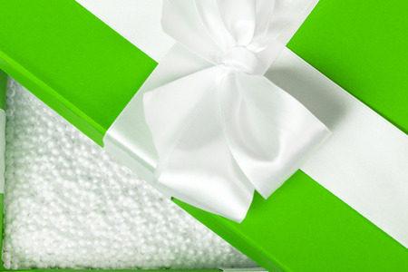 Opened green fancy box filled with white styrofoam balls. Packing for fragile present. Close shot.