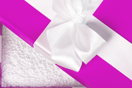 Opened pink fancy box filled with white styrofoam balls. Safety package for fragile items. Close shot.