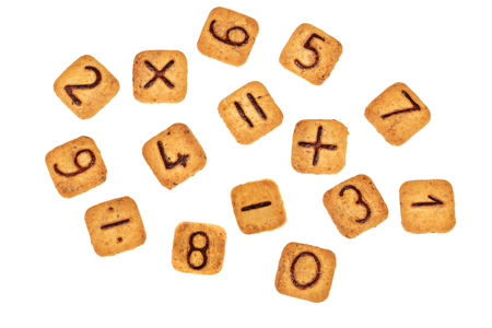 Square cookies with chocolate numbers and mathematical signs on them lay scattered about. Isolated on white background. Figures from zero to nine. Flat lay. Top view. Stock Photo