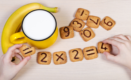 Healthy breakfast for a school children. Milk, banana and funny cookies with numbers. Childs hands doing sums using biscuits. Idea of easy arithmetics during eating. Top view.