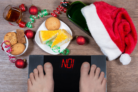 """Wagi cyfrowe z męskimi stopami i napisem """"nie!"""" otoczony świątecznymi dekoracjami, słodyczami i butelką alkoholu. Pokazuje, jak niezdrowy tryb życia podczas świąt wpływa na nasz organizm. Widok z góry. Zdjęcie Seryjne"""