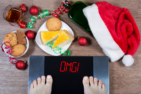 Female feet on digital scales with sign omg! surrounded by Christmas decorations, bottle, glass of alcohol and sweets. Consequences of overeating and unhealthy lifestile during holidays. Top view.