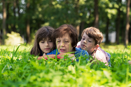 Elderly woman, girl and boy are lying on the lawn and reading a book against green nature background. Grandmother and grandchildren. Concept of harmony relationship in family.