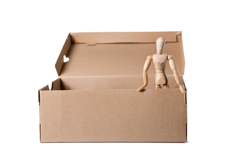 Brown cardboard box with wooden mannikin standing in it. Concept of thinking outside the box, freedom. Isolated on white background.