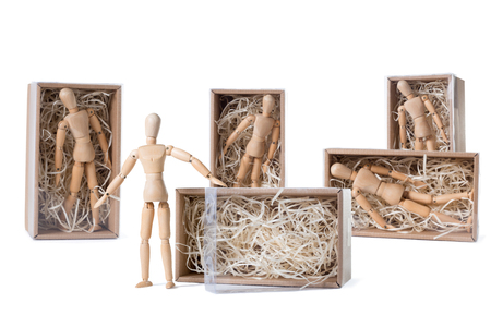 Wooden mannikin is standing near open cardboard box filled with wood shred while others are remaining inside. Concept of thinking outside the box, freedom, leadership. Isolated on white background.  Stock Photo