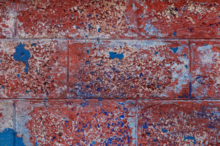 Vintage brick wall background. Brick texture with several layers of peeled paint. Old crumbling wall. Close shot. Stok Fotoğraf