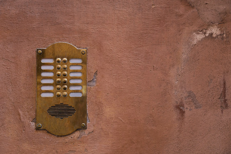 Old bronze intercom on an old wall with peeling paint. Vintage background.