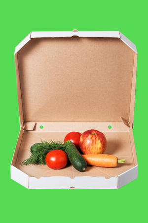 Weight loss and healthy eating or dieting concept. Open pizza box with raw vegetables in it isolated on green background. Choice of healthy food instead of junk food.